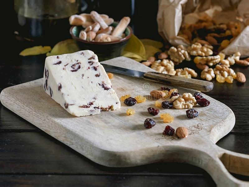 Creamery cheese with cranberries, nuts and raisins on wooden cutting board. Creamery cheese with cranberries, nuts and raisins on wooden cutting board royalty free stock image