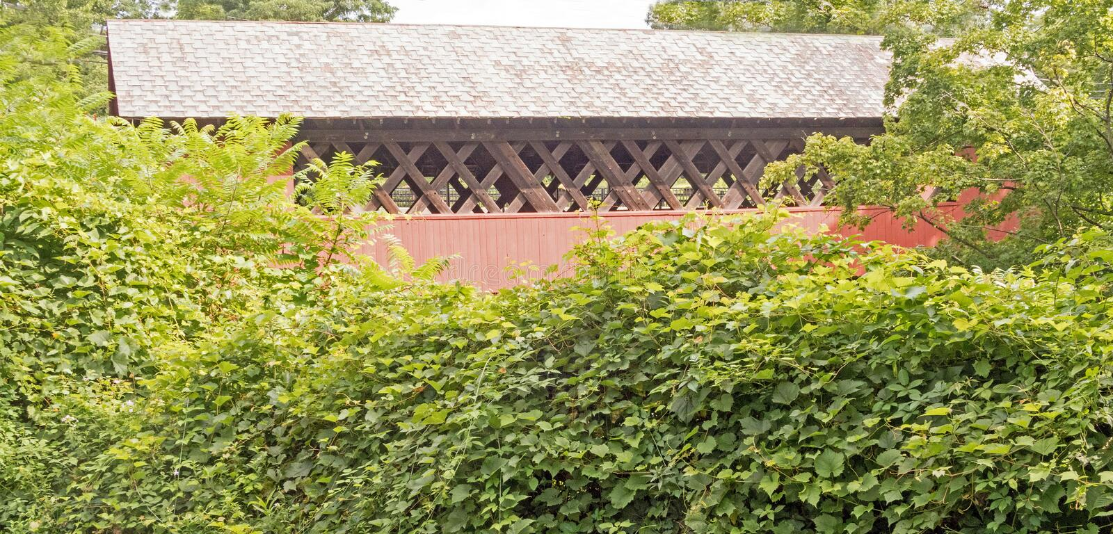 Creamery Covered Bridge. 1879 historic covered bridge West Brattleboro, Vermont, lattice truss, across Whetstone Brook hidden by vegetation royalty free stock photography