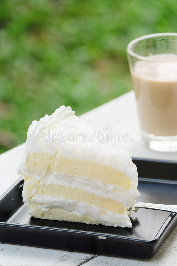 Creamy coconut cake with a cup of milk tea royalty free stock photography
