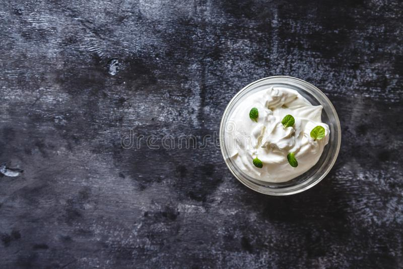 Creamy curd cream yogurt with mint in a bowl on a dark retro background. Top view.  royalty free stock photo