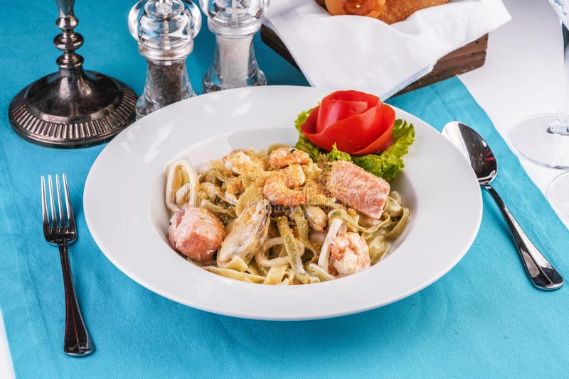 Creamy pasta with shrimps, crab meat, seafood, squid rings, tomatoes, basil, greens and cheese стоковое изображение