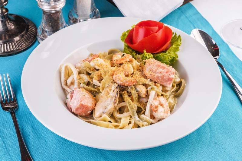 Creamy pasta with shrimps, crab meat, seafood, squid rings, tomatoes, basil, greens and cheese стоковая фотография