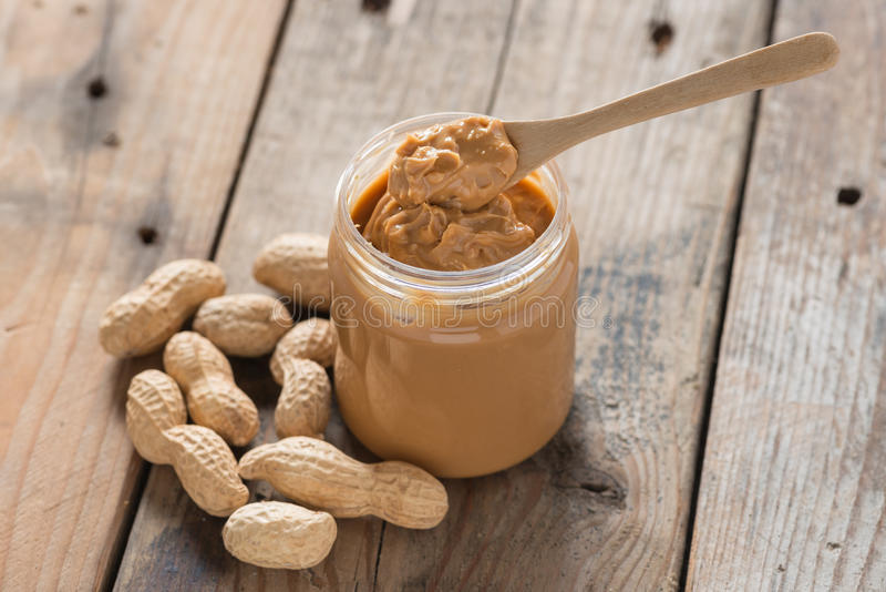 Creamy peanut butter with spoon on wood table. Selective focus. stock images