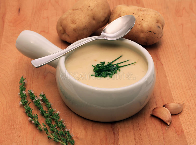Creamy potato and onion soup. Cream of potato and onion soup, served hot with a chopped chive garnish royalty free stock photos