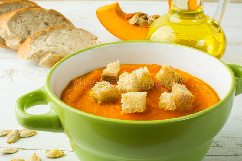 Creamy pumpkin soup with croutons in a green bowl stock photo