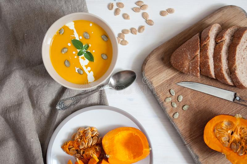 Creamy pumpkin soupwith pumpkin seeds and green, bread with bran and sliced pumpkin on wooden and fabric background. Top stock images