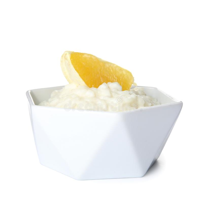 Creamy rice pudding with orange slice in bowl. On white background royalty free stock image