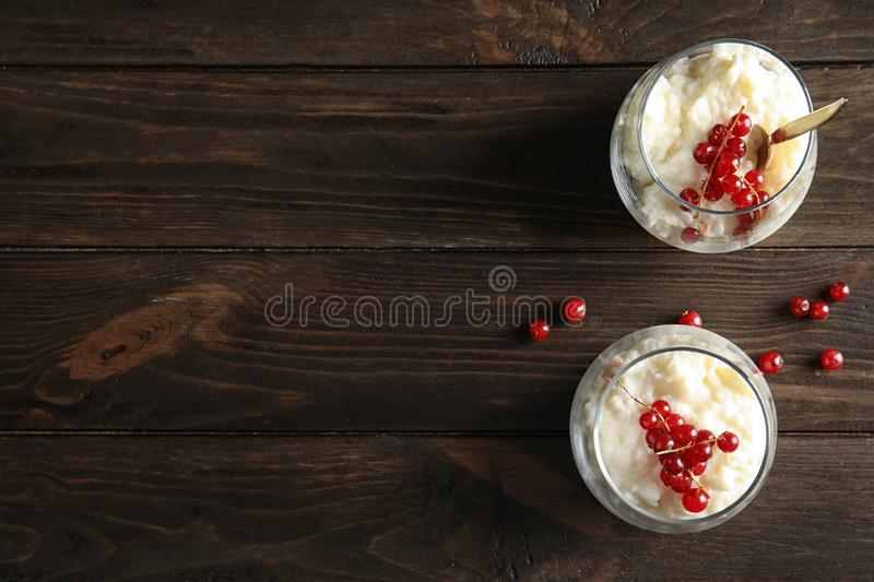 Creamy rice pudding with red currant in glasses and berries on wooden background, top view stock image