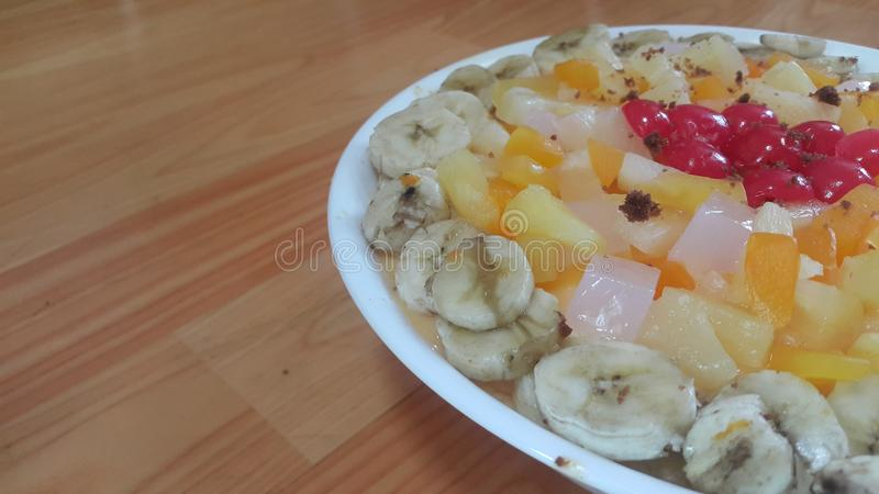 Creamy tasty sweet fruit trifle with banana slices layered on surface. Creamy tasty sweet fruit trifle over custard with banana slices layered on surface on royalty free stock photography