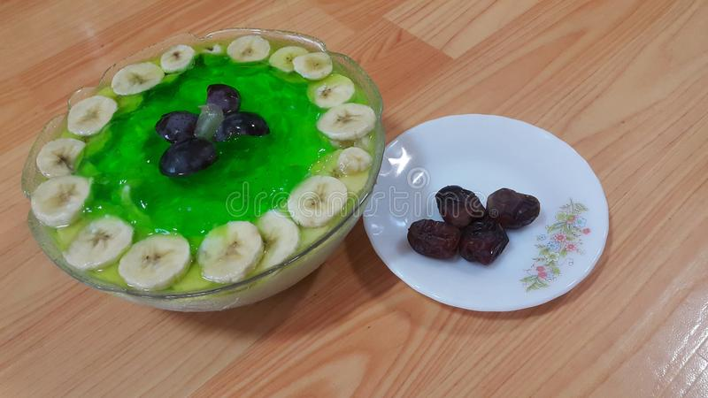 Creamy tasty sweet green jelly with banana slices layered on surface. Creamy tasty sweet green jelly over custard with banana slices layered on surface on wooden royalty free stock images