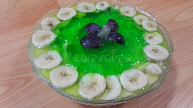 Creamy tasty sweet green jelly with banana slices layered on surface. Creamy tasty sweet green jelly over custard with banana slices layered on surface on wooden royalty free stock photography
