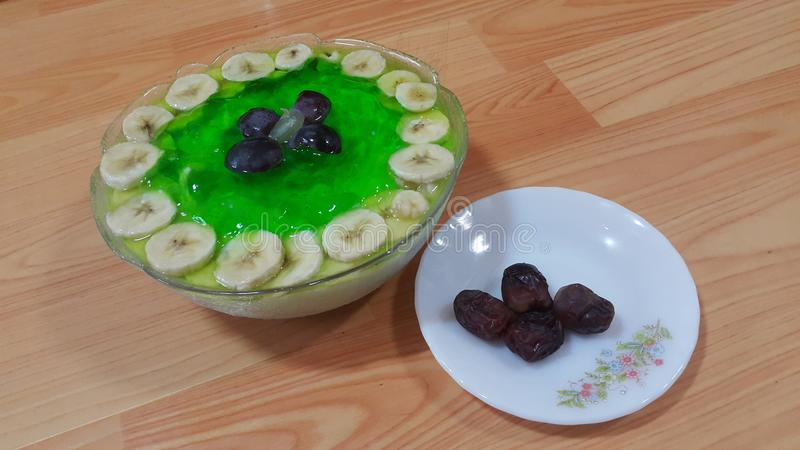 Creamy tasty sweet green jelly with banana slices layered on surface. Creamy tasty sweet green jelly over custard with banana slices layered on surface on wooden stock image