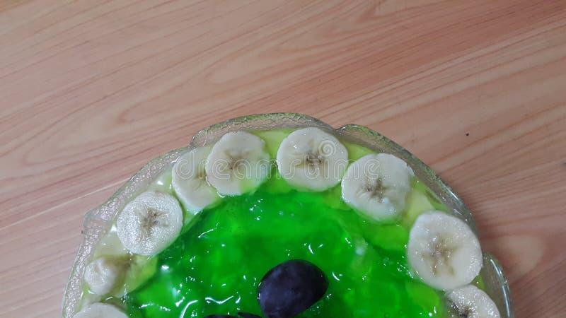 Creamy tasty sweet green jelly with banana slices layered on surface. Creamy tasty sweet green jelly over custard with banana slices layered on surface on wooden stock photos