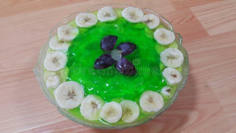 Creamy tasty sweet green jelly with banana slices layered on surface. Creamy tasty sweet green jelly over custard with banana slices layered on surface on wooden royalty free stock photo