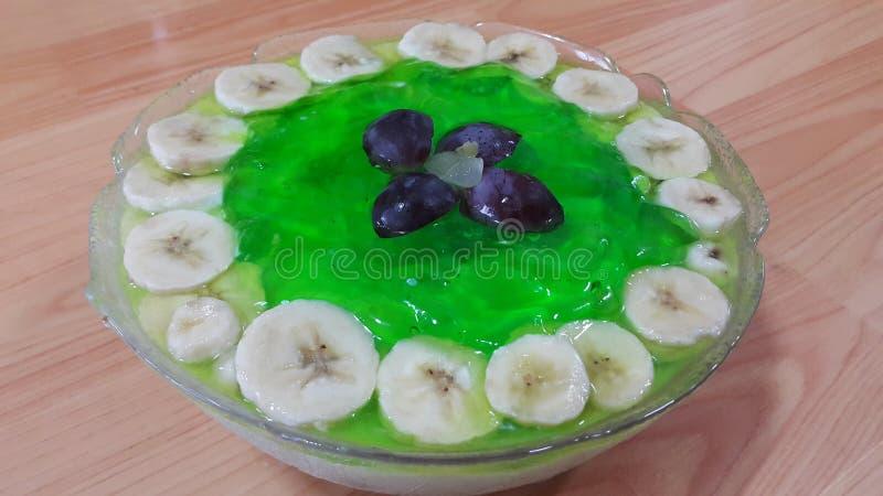 Creamy tasty sweet green jelly with banana slices layered on surface. Creamy tasty sweet green jelly over custard with banana slices layered on surface on wooden stock photo
