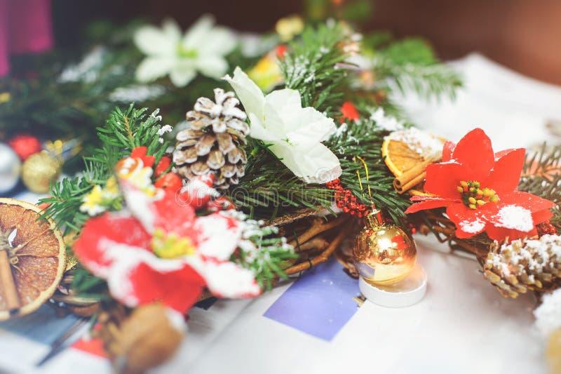 Creando una guirnalda de la Navidad hecha de ramas del abeto, de bayas ornamentales, de conos del pino y de juguetes decorativos  imagenes de archivo