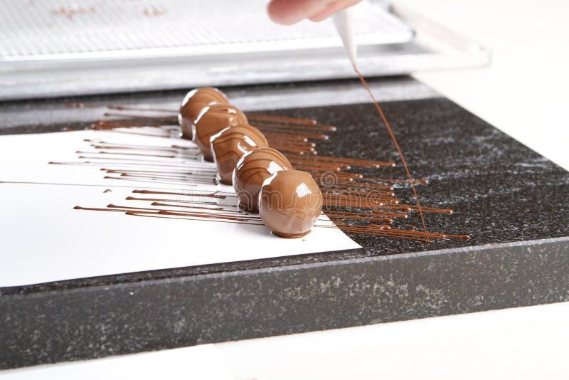 Creare le praline ed i tartufi con cioccolato al latte fotografie stock