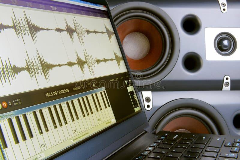 Creare musica in un redattore sul computer portatile, altoparlanti vaghi del fondo immagine stock libera da diritti