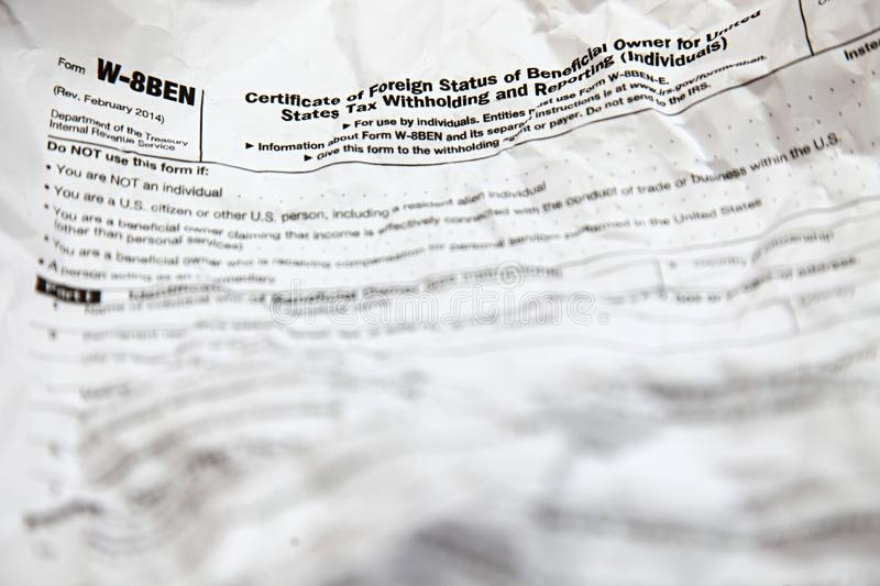 Creased W8BEN form. Crumpled W8BEN form, the certificate of foreign status of beneficial owner for United States tax withholding and reporting for individuals royalty free stock photos