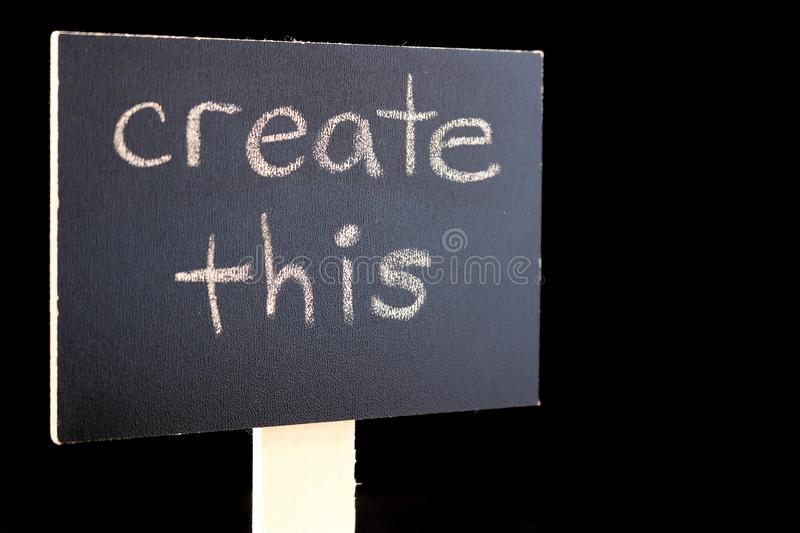 Create This - chalkboard sign on black background. Chalkboard or blackboard sign with `create this` text - good for social media posts, blogs, internet royalty free stock photo