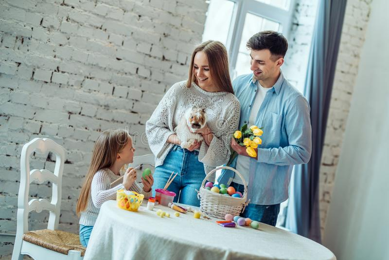 Create an Easter atmosphere together.Loving family tells their daughter about the Easter bunny and traditions of the holiday royalty free stock photos