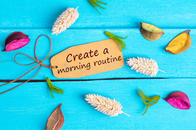 Create a morning routine text on paper tag. With rope and color dried flowers around on blue wooden background royalty free stock photography