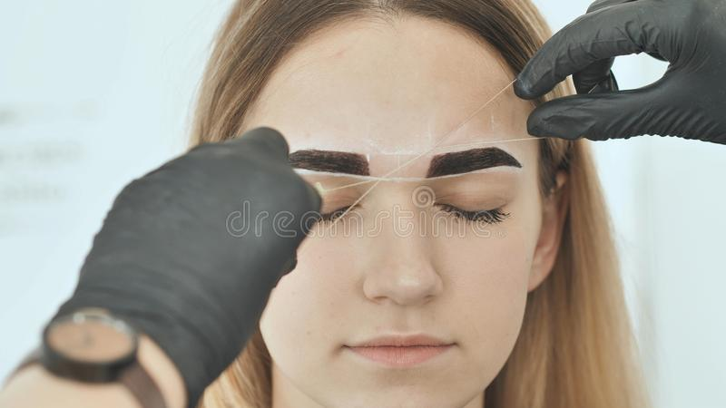 Create permanent eyebrow makeup. Create permanent eyebrow makeup. Thread depilation. stock photos
