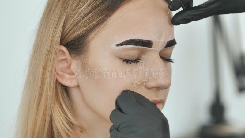 Create permanent eyebrow makeup. Create permanent eyebrow makeup. Thread depilation. stock photography