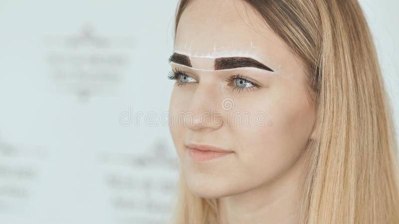 Create permanent eyebrow makeup. Marking the shape of the eyebrows. royalty free stock photos