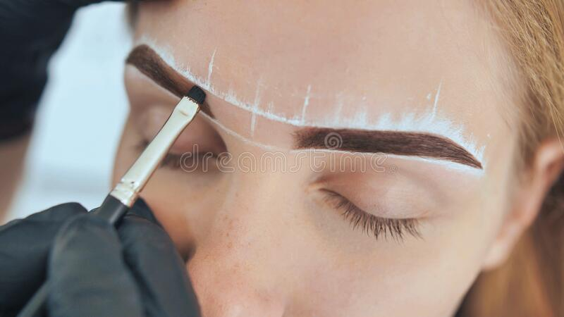 Create permanent eyebrow makeup. Marking the shape of the eyebrows. royalty free stock photography