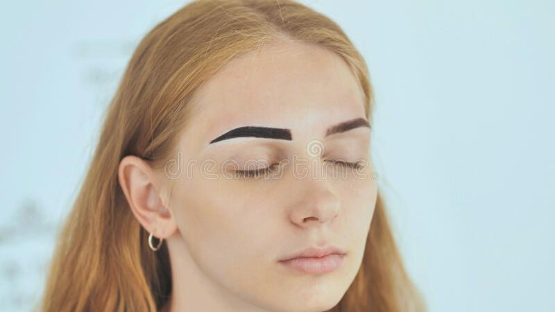 Create permanent eyebrow makeup. Marking the shape of the eyebrows. stock photo