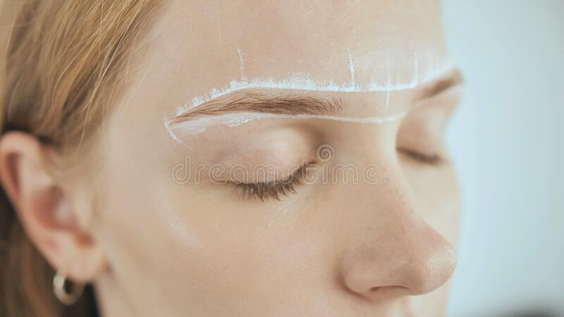 Create permanent eyebrow makeup. Marking the shape of the eyebrows. royalty free stock photo
