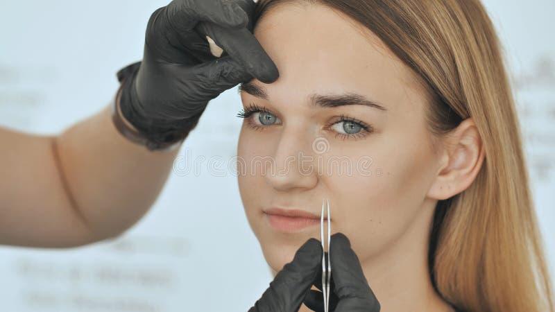 Create permanent eyebrow makeup. Peeling with tweezers. royalty free stock photos