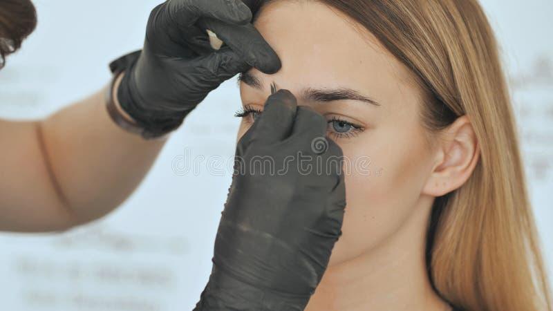 Create permanent eyebrow makeup. Peeling with tweezers. stock photo