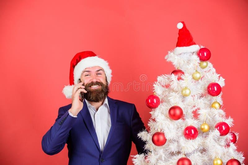 Create santa nennt diese Weihnachtszeit Kleideranzug und Santa-Hut-Handy Manager gratuliert den mobilen Mitarbeitern lizenzfreies stockfoto