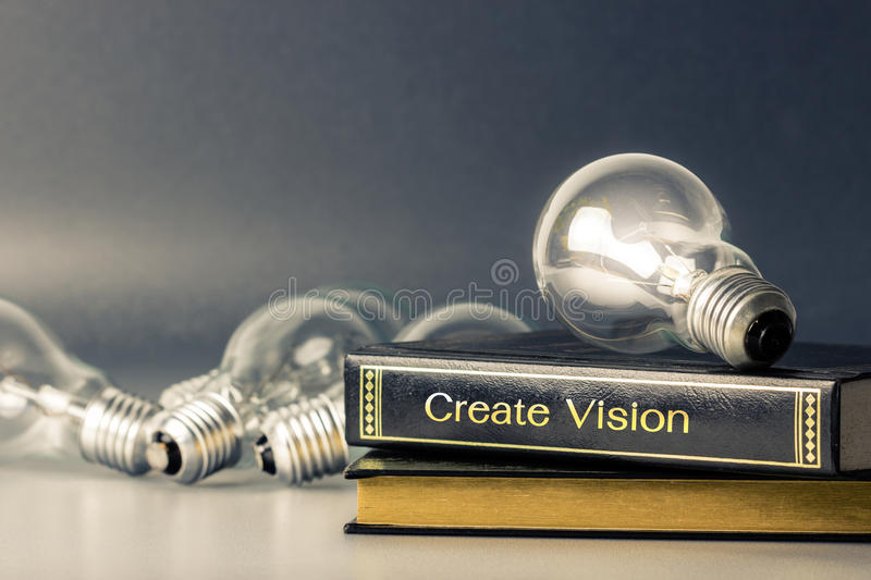 Create vision. Light bulbs glowing on the book of vision stock photo