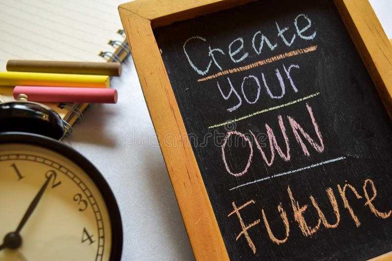 Create your own future on phrase colorful handwritten on chalkboard, alarm clock with motivation and education concepts. stock photography