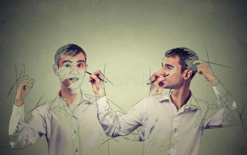 Create yourself concept. Man drawing a picture, sketch of himself. Create yourself concept. Good looking young man drawing a picture, sketch of himself on grey royalty free stock photography