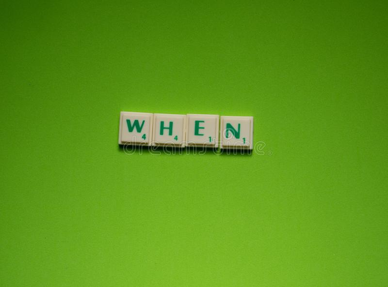 Created word of `when` on the green background. Created word of `when` with the letters on the green screen background stock photo