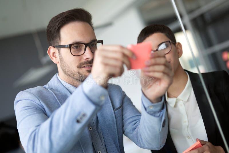 Creatief commercieel team dat kleverige nota's over venster bekijkt stock foto