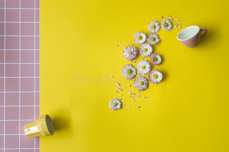 Creatief concept met een roze kop en bloemen op een gele achtergrond royalty-vrije stock afbeeldingen