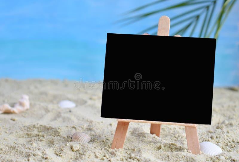 Creatief minimaal de zomeridee Bord op zand met onduidelijk beeld blauwe overzees en tropisch palmblad De verkoopconcept van de v royalty-vrije stock afbeeldingen