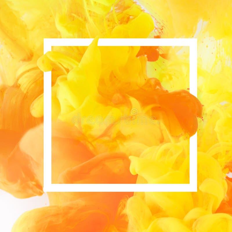 creatief ontwerp met stromende gele en oranje verf in wit vierkant kader stock foto