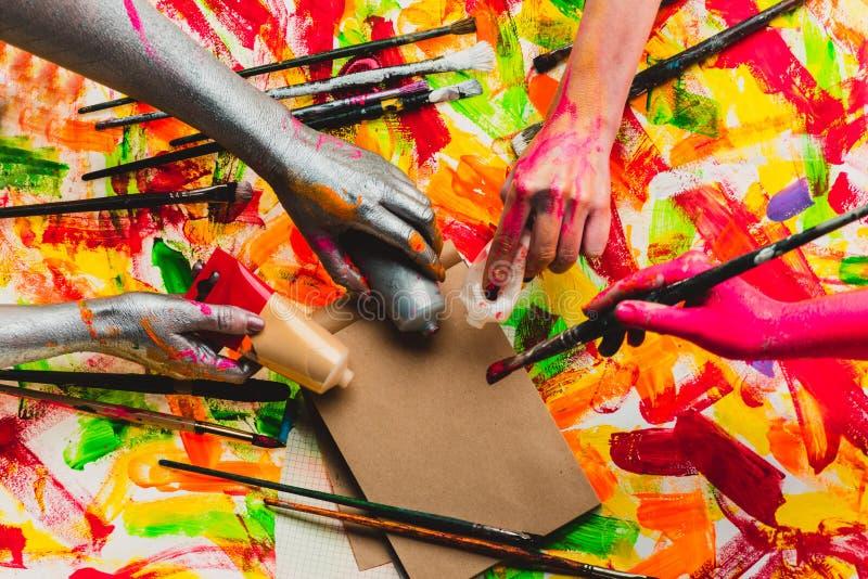 Creatief project Mooie achtergrond Art Collective Teambuilding Vier gekleurde handen Veelkleurige foto stock afbeelding