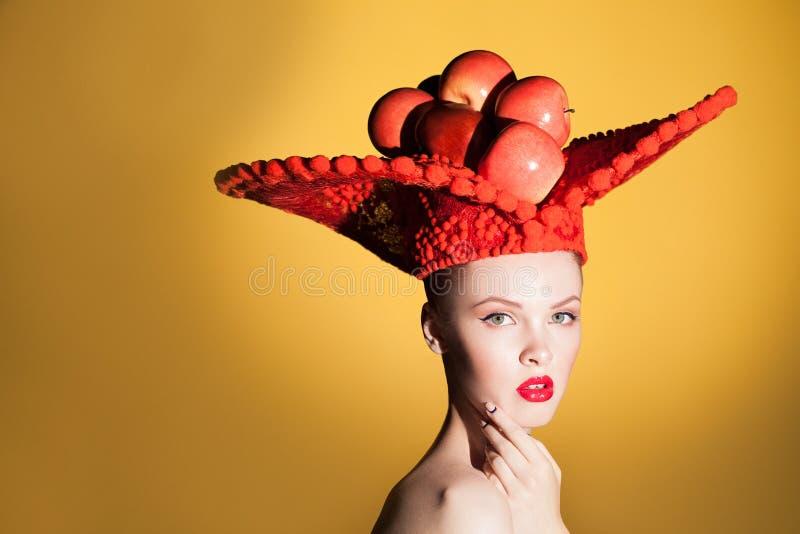 Creatief schoonheidsportret van jonge mooie vrouw die camera bekijken en in studio bij grote rode hoed met rode appelen stellen royalty-vrije stock foto's