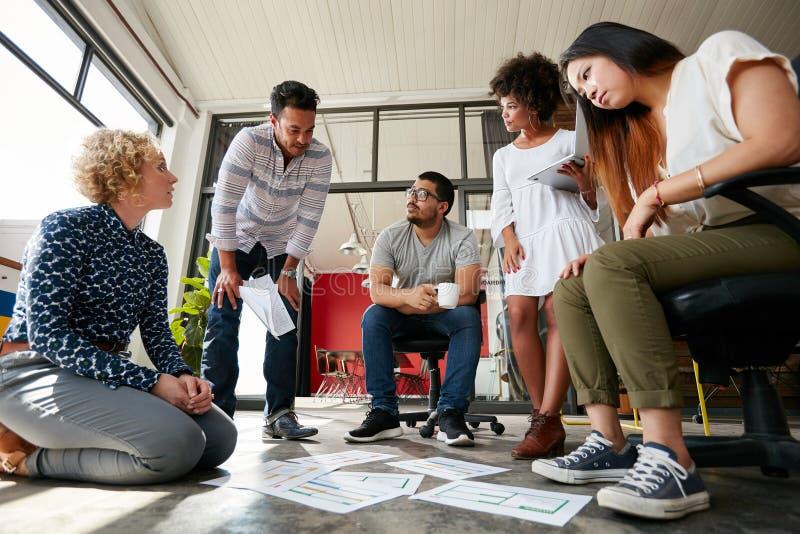 Creatief team die aan vloer bij het werkruimte werken stock fotografie