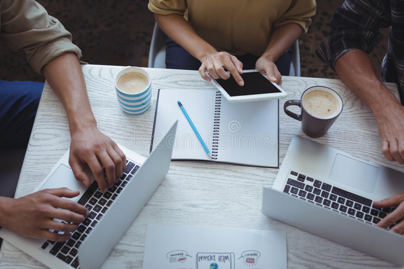 Creatief team die laptop en digitale tablet gebruiken terwijl planning in bureau stock foto