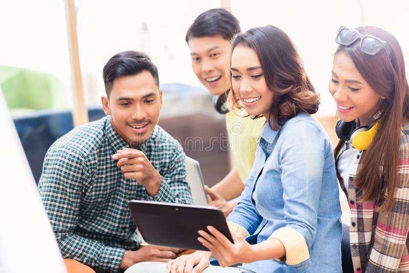Creatief team die op een verrassende bedrijfspresentatie op lusje letten stock foto