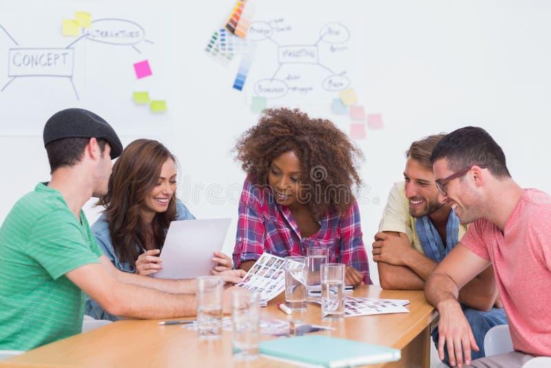 Creatief team die over contactbladen gaan in vergadering stock foto
