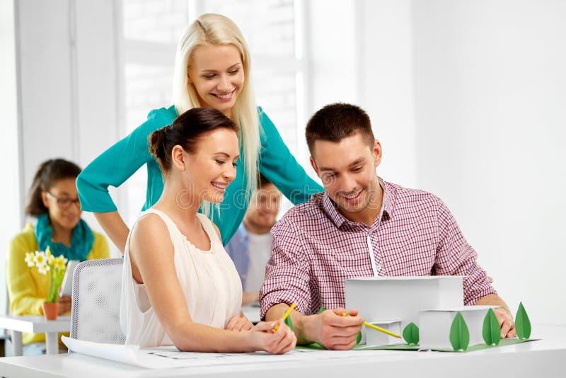 Creatief team met blauwdruk die op kantoor werken stock fotografie